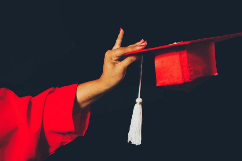 Closeup of a hand holding a graduation cap.