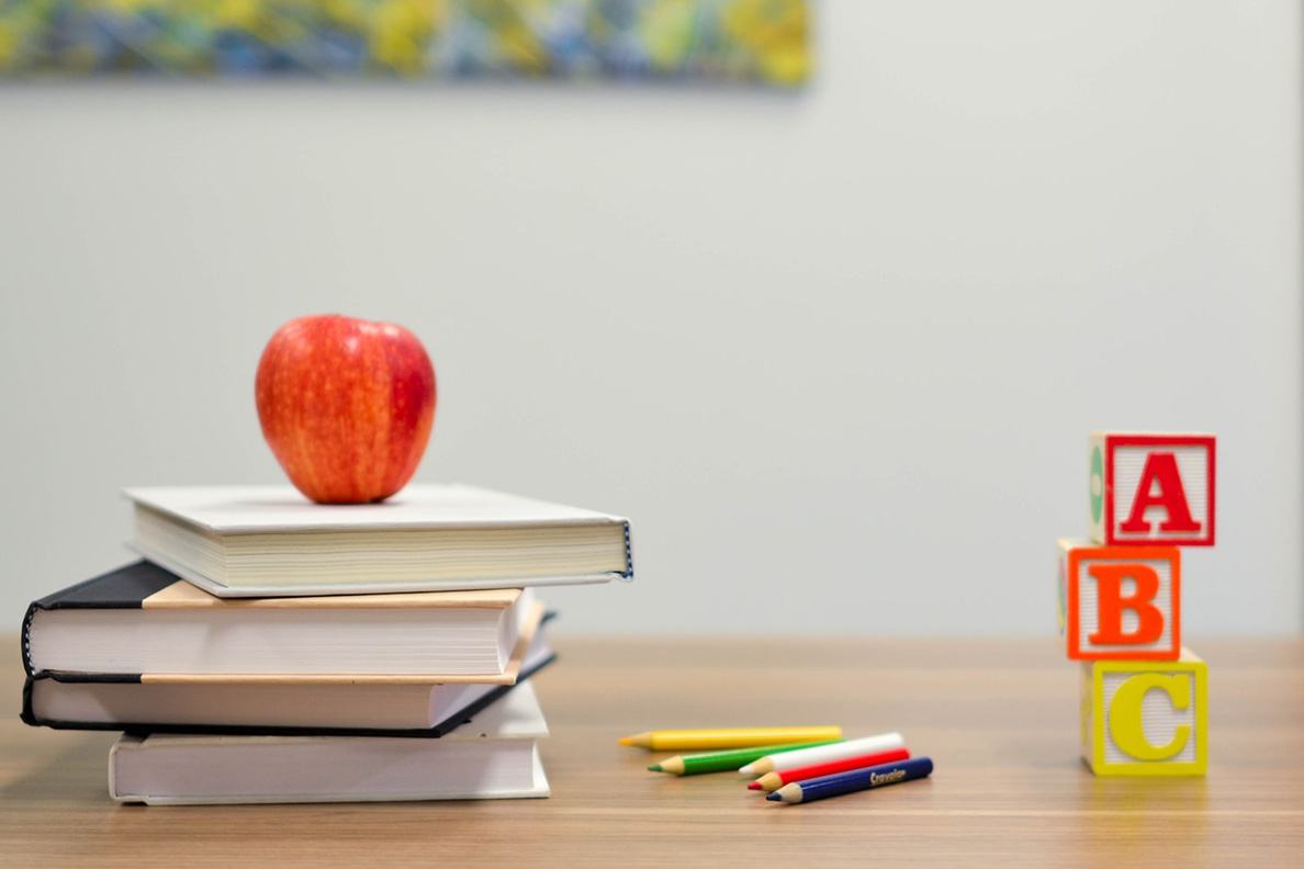A stack of books with an apple on top next to colored pencils and a stack of ABC blocks