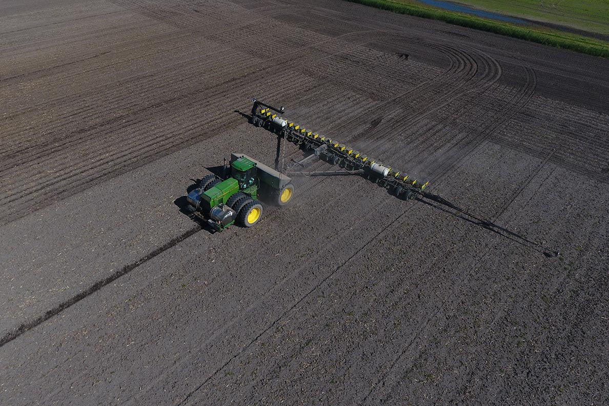 a tractor tilling a field of soil viewed from above