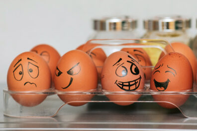 Brown eggs with different emotional facial expressions drawn on them.