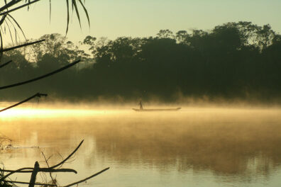 A person standing on a canoe with a pole as golden mist comes off the river water
