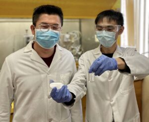 Two male scientists in lab coats and masks. one scientist is holding a petry dish and a test tube.