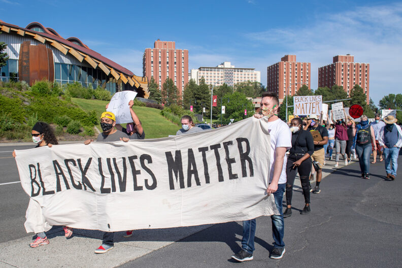 Black Lives Matter supporters march near the WSU Pullman campus with signs and banners.