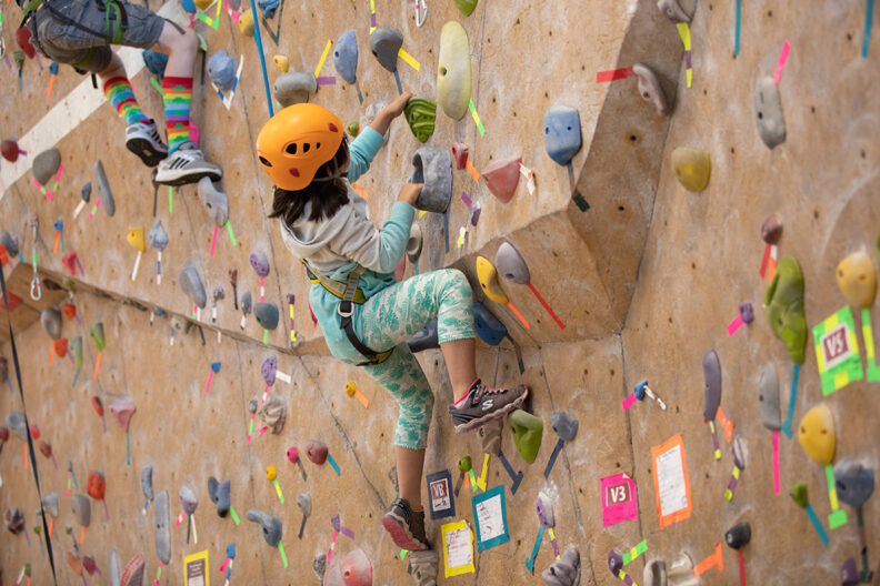 A kid makes her way up a climbing wall