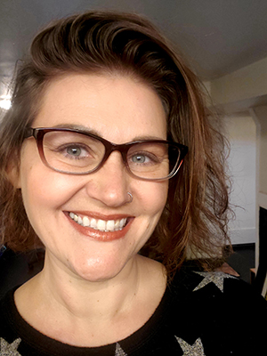 portrait of woman with brown hair and glasses