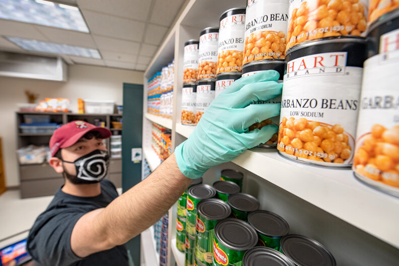 A food bank volunteer stocking shelves with canned food.