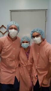 Three medical professionals pose for a picture in surgical wear