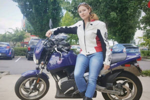 Closeup of Allison Coffin standing in front of a motorcycle.