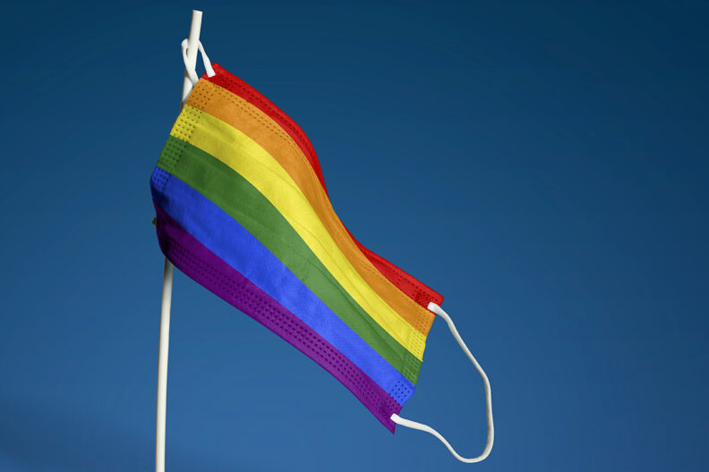 A face mask resembling an LGBTQ pride flag hanging from a stick in front of a blue background.