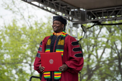 Abel Saba smiles as he holds a WSU diploma during an outdoor commencement ceremony.