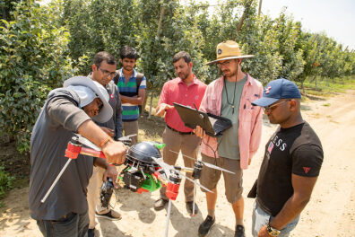 Six people standing in an orchard and inspecting a drone.