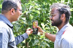 Lav Khot and Rakesh Ranjan looking at a smartphone using their new app