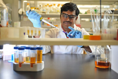 Kathir Selvam in a research lab holding a pipette.