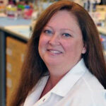woman with long red hair and a lab coat