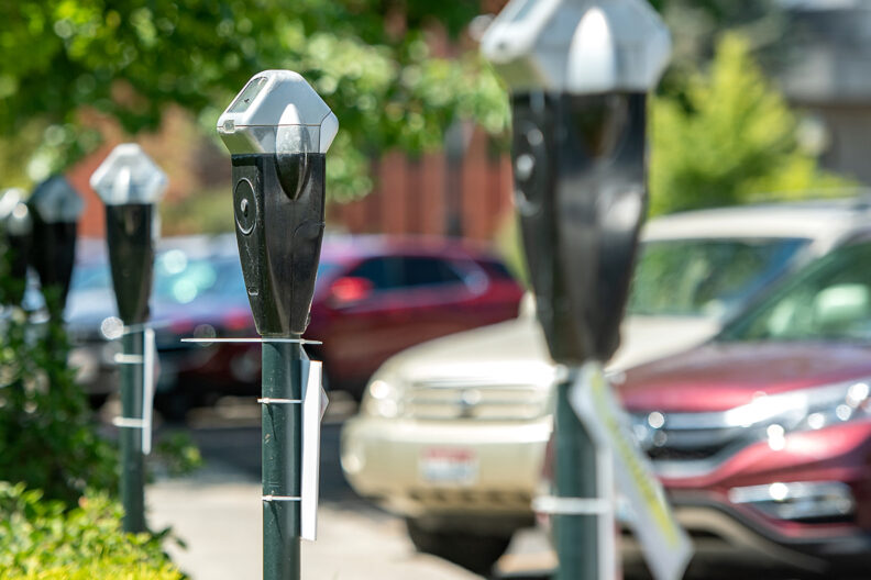 Closeup of a line of parking meters in front of parked cars on the WSU Pullman campus.