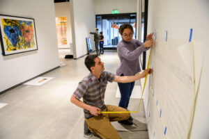Ryan Hardesty and an intern install art on a wall.
