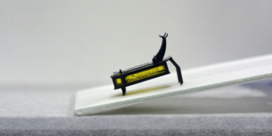 A robotic beetle sits idle on a small incline.