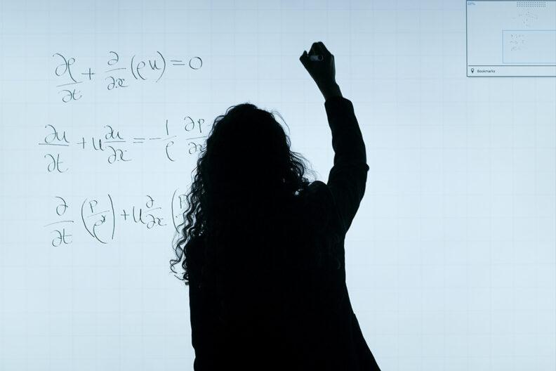 A math teacher writes on a white board