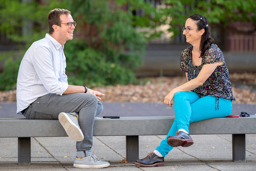 Matthew Jeffries and Nitivia Jones sitting on a bench outside on the WSU Pullman campus.