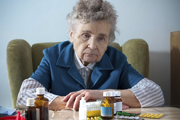 A photo of an old woman sitting with a bunch of medications on a table