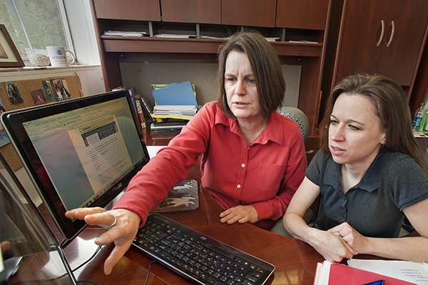 A photo of two women looking at information on a computer