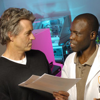 A closeup of a researcher talking to a man