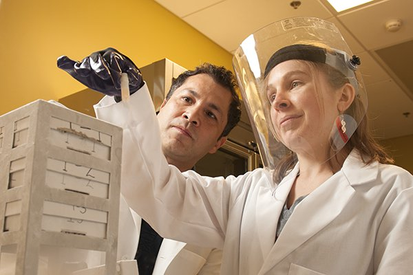 A photo of a two researchers doing an experiment in a lab