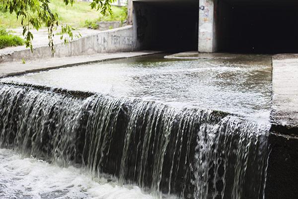A photo of a urban runoff under a bridge