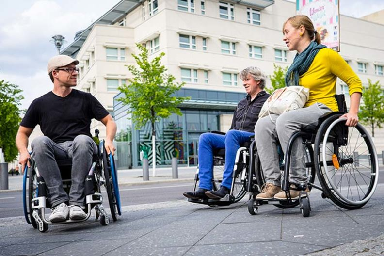 A photo of three people in wheelchairs