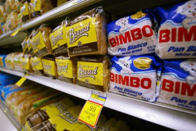 ** FILE ** Albertsons' brand wheat bread, left, is seen competing against the Mexican-imported white bread made by Bimbo on the selves of a Super Savers market in this April 24, 2003 file photo in Anaheim, Calif. Go ahead, have a piece of bread. Have three. Make it whole-grain, and you'll be following government advice for eating right. Three servings of whole grains each day will reduce your risk of heart disease and type 2 diabetes, according to scientists and doctors who wrote the new federal food guidelines. You may also keep from gaining weight. .(AP Photo/Damian Dovarganes, Files)
