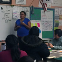 A photo of a parent talking at the front in a classroom of adults