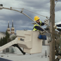 Power workers up on a light pole