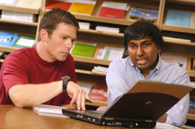 Two students looking at survey results on a laptop.
