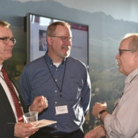 A group photo of three faculty members having a conversation at the Recognition Reception