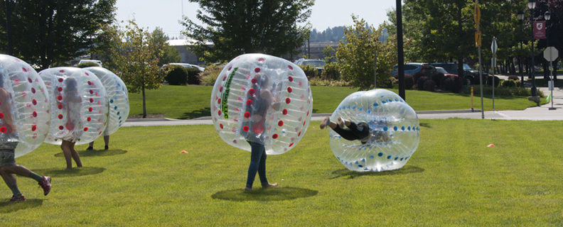 Picture of students playing a game on the lawn with people-sized plastic balls