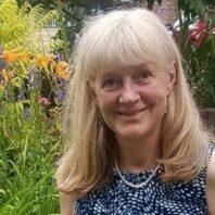 Woman with medium length blonde white hair, smiling