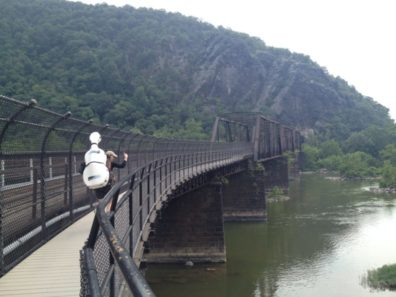 Ruth Boden backpacks with her cello across the historic Potomac River railroad bridge on the Appalachian Trail in Harpers Ferry, WV. Photo credit: Dean Luethi