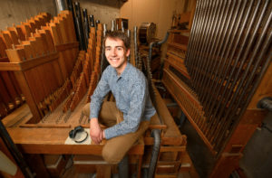 thomas-leclair-sits-among-the-many-pipes-of-the-old-organ-in-the-basement-of-webster-hall