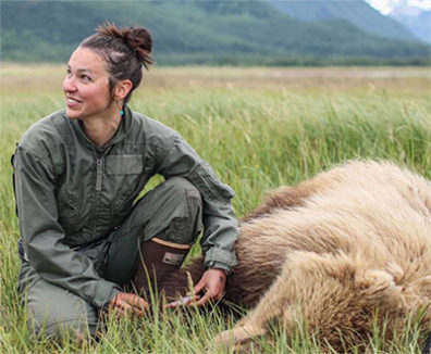 Woman tending to a sedated bear in a meadow surrounded by mountains.
