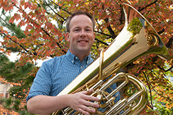 Chris Dickey holding a shiny brass tuba in front of a colorful tree.