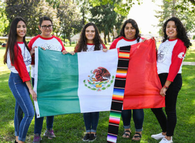 Fiveyoung women hold a Mexican flag and colorful drape.