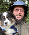 Todd Wilson with a pretty, tri-color shepherd or collie puppy.