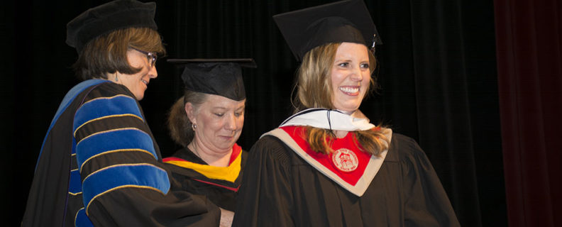 faculty helping a student during commencement ceremony