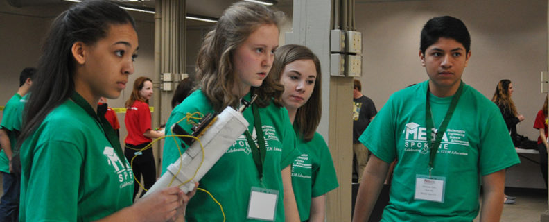 four students on green shirt team in mesa prosthetic arm training