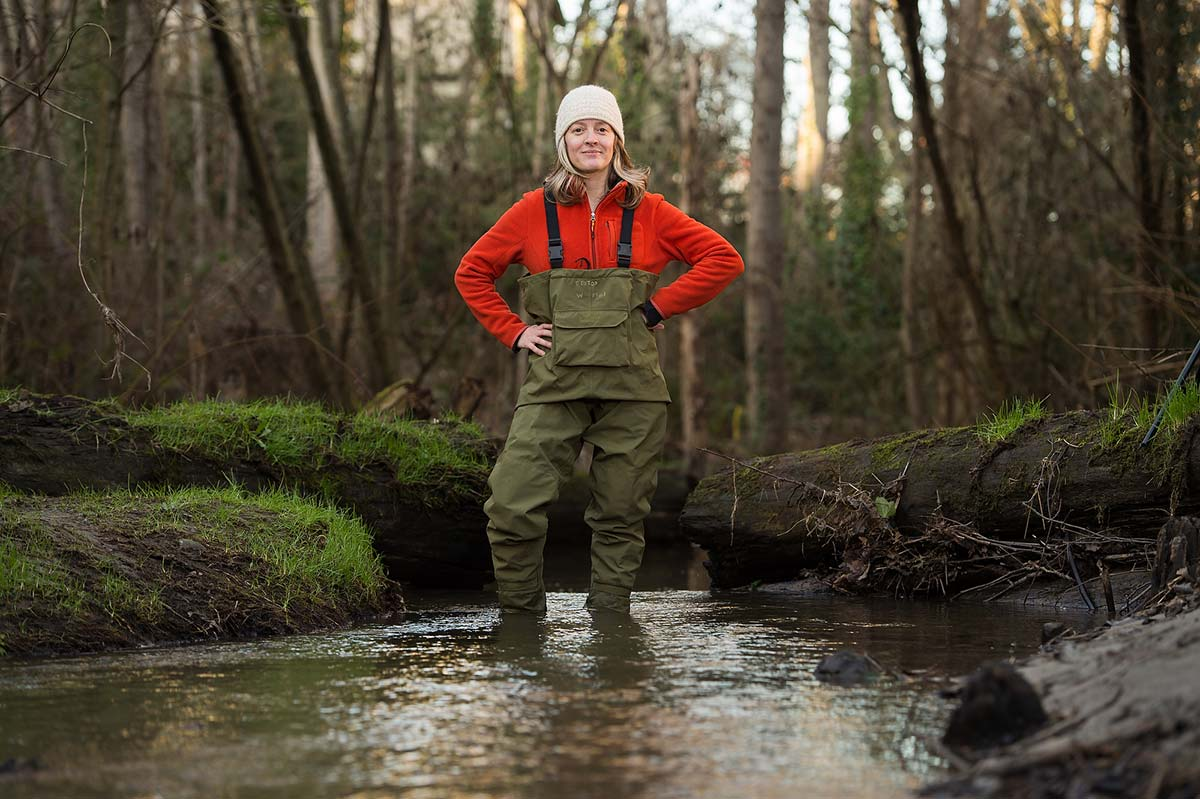 Female researcher, Jen McIntyre, standing in stream