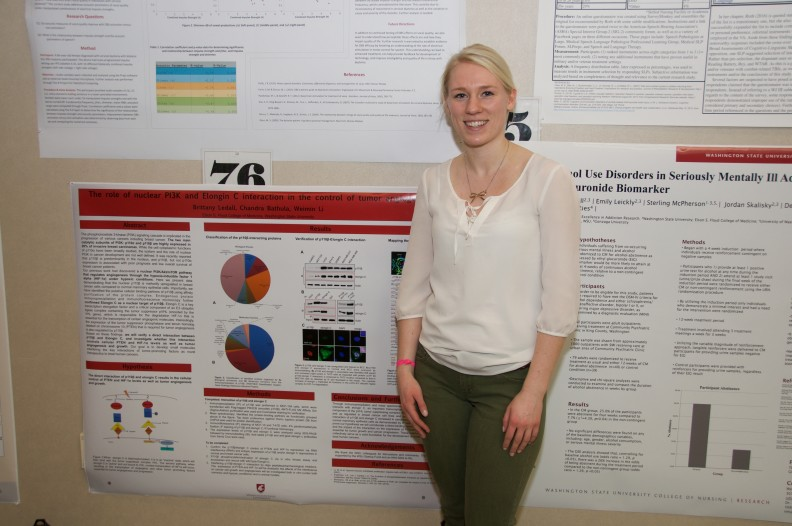 Brittany Ledall stands by her poster at the Inland Northwest Research Symposium at WSU Spokane on April 1, 2016.