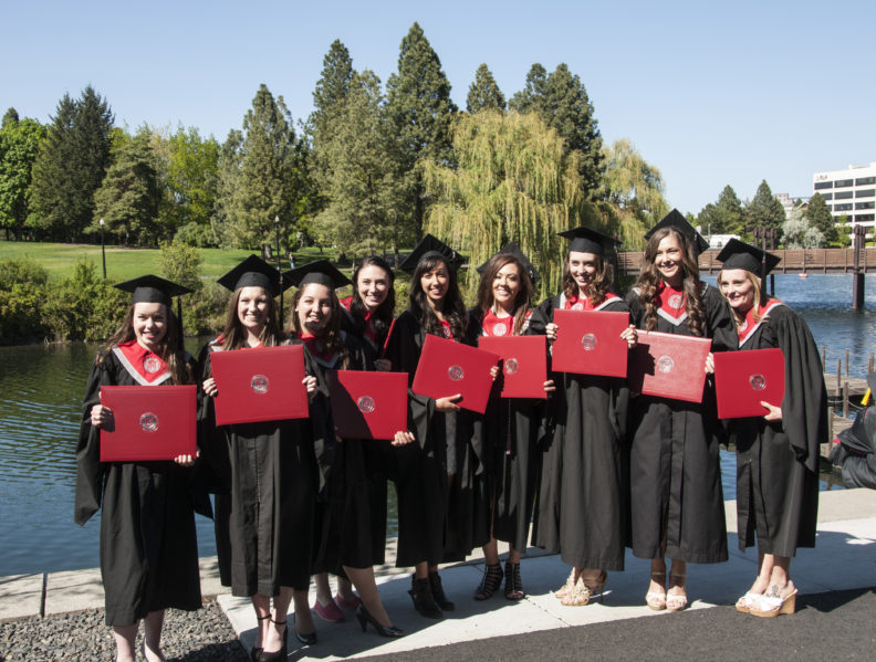 WSU Spokane students show off their diplomas after the 2015 commencement ceremony.