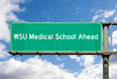 "This is a graphic that portrays a green highway sign saying ""WSU Medical School Ahead""."
