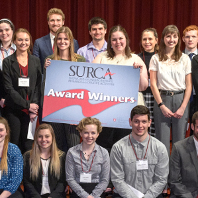 Group photo of SURCA 2019 award winners posing on stage in the CUB auditorium.