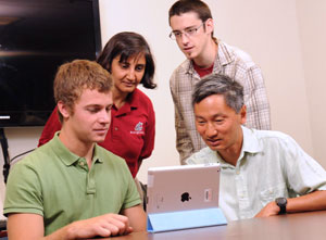 Professors and students looking at tablet PC